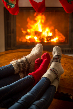 fireplace family: Family wearing knitted socks sitting in chalet by burning fireplace
