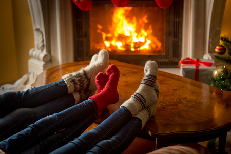burning fireplace: Beautiful image of family feet in woolen socks resting next to the burning fireplace