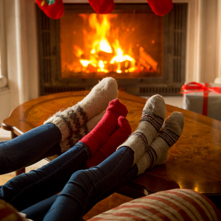 burning house: Closeup image of family in knitted woolen socks warming at burning fireplace at house