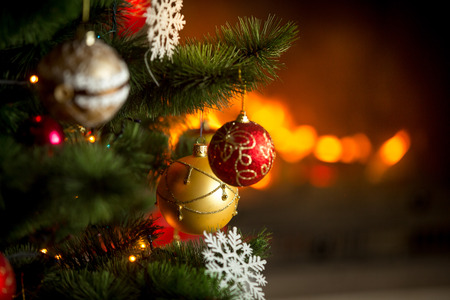 burning fireplace: Closeup image of red and golden baubles hanging on Christmas tree on background of burning fireplace