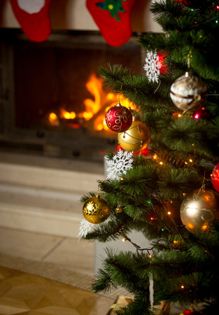 christmastime: Beautiful background of decorated Christmas tree in front of burning fireplace at house Stock Photo