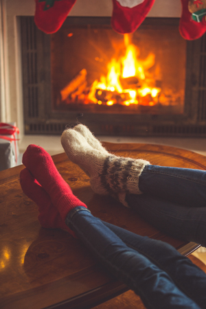hearthside: Toned image of couple wearing woolen socks relaxing at burning fireplace at Christmas
