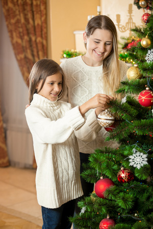 decorate: Cute girl helping mother to decorate Christmas tree at living room