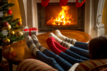 Feet of family in woolen socks warming near burning fireplace at living room on Christmas 免版税图像