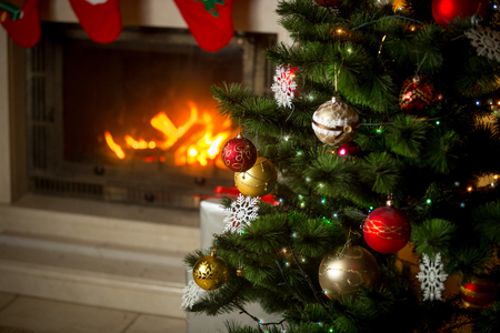 burning fireplace: Beautiful decorated Christmas tree in front of burning fireplace at house. Focus on fireplace