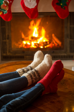 burning fireplace: Closeup image of male and female feet in woolen socks warming at burning fireplace