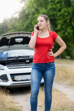 calling for help: Portrait of frustrated woman calling for help with her broken car at rural road Stock Photo