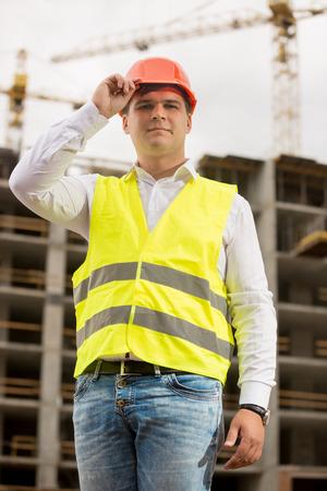 taskmaster: Portrait of handsome smiling engineer in hardhat posing against working construction crane