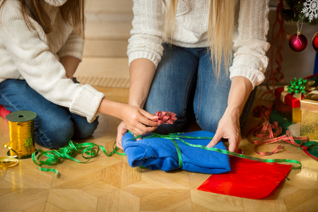 warm clothing: Closeup image of young woman and girl wrapping sweater in decorative paper and colorful ribbons