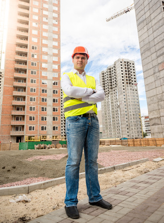 taskmaster: Portrait of smiling young architect standing at building place