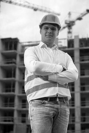 Black and white portrait of smiling architect in hardhat standing against building under construction