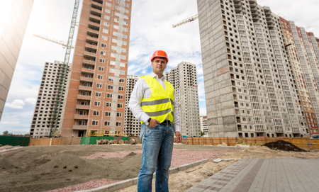 taskmaster: Image of young engineer in hardhat and safety vest posing against buildings under construction