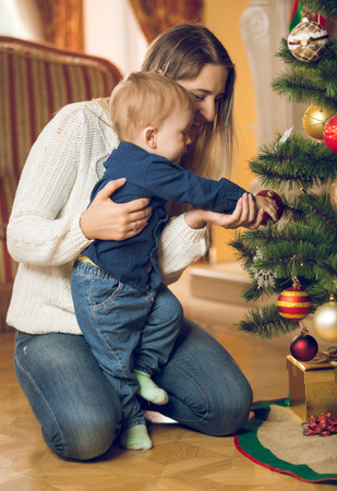rom: Happy young mother with her 10 months old baby boy decorating Christmas tree at living rom