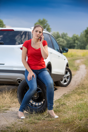 calling for help: Young woman sitting on the spare tire at roadside and calling for help