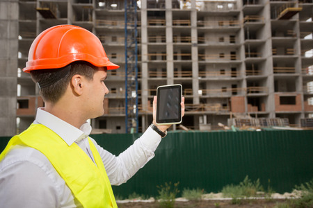 Rear view of construction engineer controlling building construction with digital tablet