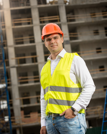 taskmaster: Portrait of young construction engineer standing at building site and looking at camera Stock Photo