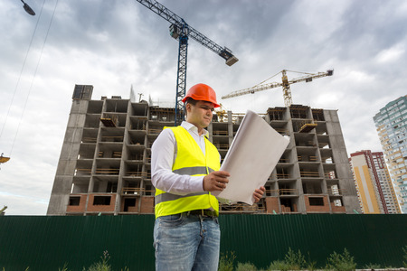 foreman: Portrait of foreman looking on blueprints at building site