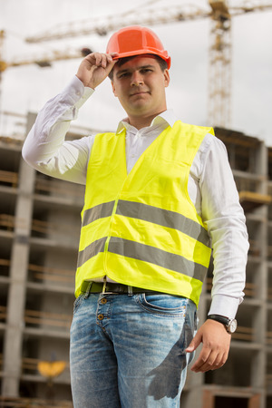 Toned closeup portrait of smiling construction engineer wearing hardhat Stock Photo