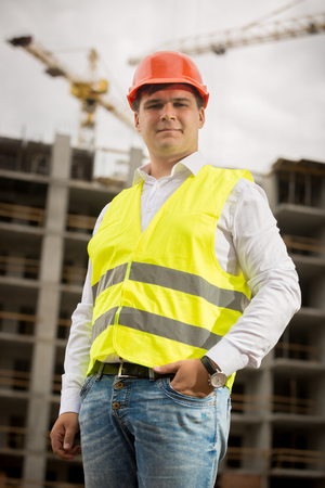 Portrait of smiling construction engineer in hardhat looking at camera