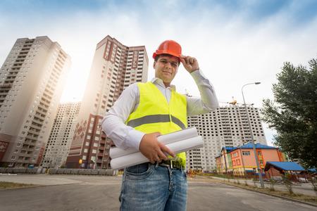 Portrait, jeune, ingénieur, debout, nouveau, bâtiments, plans Banque d'images