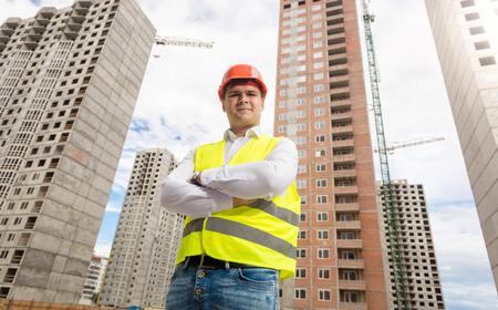 Portrait de jeune architecte hardhat et gilet de sécurité pose contre les nouveaux bâtiments