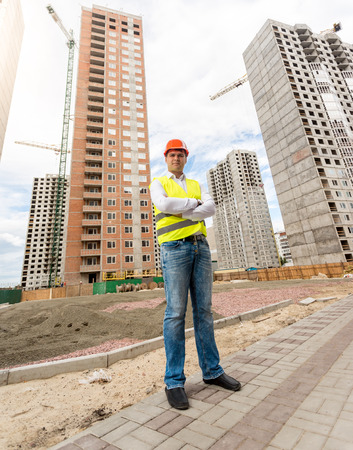 taskmaster: Young construction engineer standing in front of buildings under construction