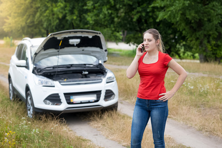 Young angry woman calling for help next to broken car in meadow