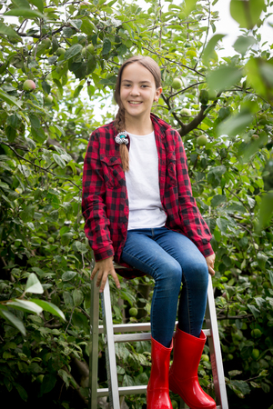 stepladder: Happy young girl in red wellington boots  sitting on stepladder at garden