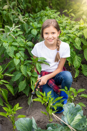 Portrait of happy young woman working at garden with trowel Stock Photo