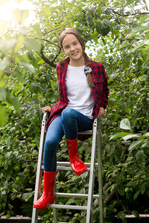 gumboots: Smiling teenage girl in red gumboots posing on ladder at apple garden