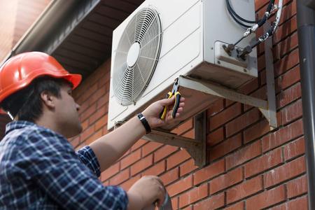 Portret van technicus in hardhat die buitenlucht airconditioning aansluit Stockfoto