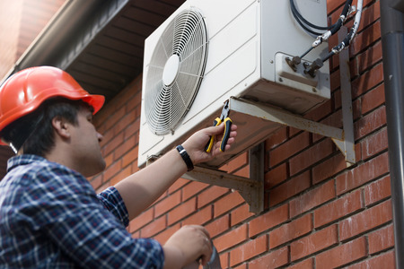Portrait of technician in hardhat connecting outdoor air conditioning unit