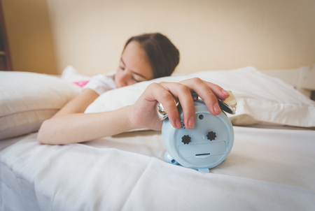 overslept: Closeup photo of young woman turning off alarm clock Stock Photo