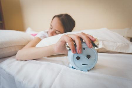 overslept: Closeup photo of young woman turning off alarm clock Stock Photo