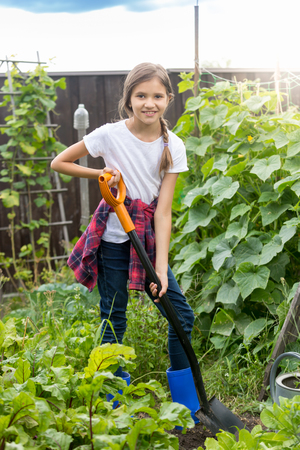 Cute 10 year old girl working at garden and digging soil at with shovel