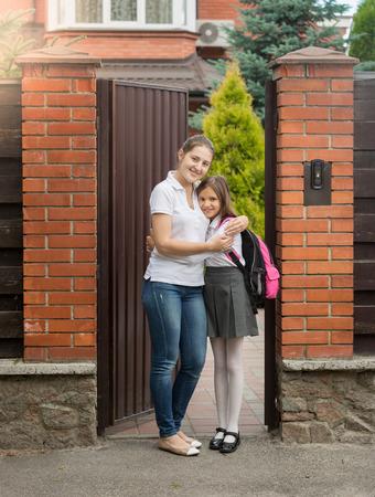 niños saliendo de la escuela: Madre joven feliz que se coloca con su hija en el uniforme escolar en el patio trasero casa