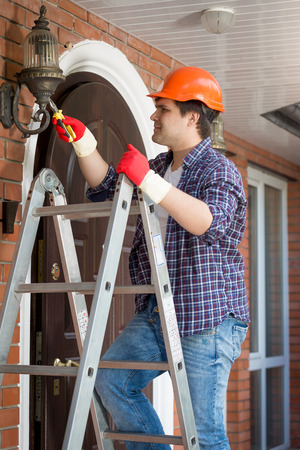 manual test equipment: Male electrician in hardhat standing stepladder and repairing lamp on house outdoor wall Stock Photo