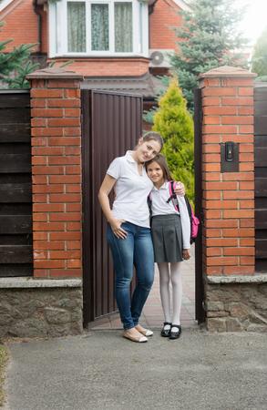 niños vistiendose: madre sonriente joven que abraza a su hija ir a la escuela frente a la casa