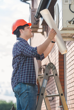 adjuster: Portrait of engineer examining air conditioning system and comparing it with plan