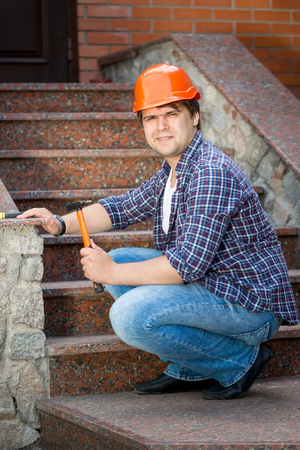 sealant: Portrait of smiling construction worker repairing stone staircase