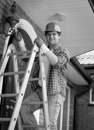 stepladder: Black and white portrait of smiling electrician posing on top of stepladder