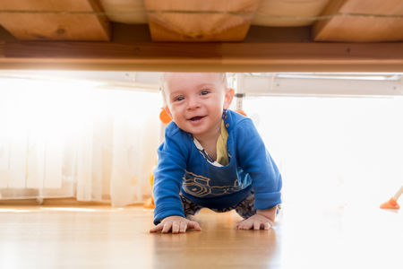 nappy new year: Portrait of cute baby boy crawling and looking under the bed Stock Photo