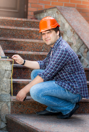sealant: Young smiling male worker measuring stone staircase with measuring tape