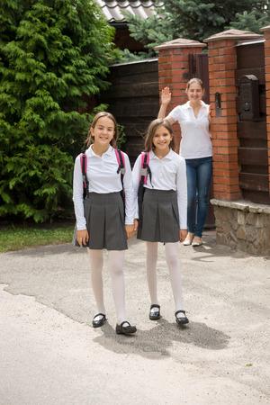 若い母親は学校に歩く娘に手と手を振って 写真素材
