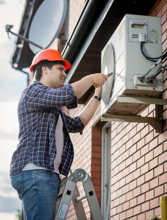 Young male technician repairing outdoor air conditioning system