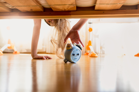 arouse: Toned photo of annoyed girl reaching for alarm clock under the bed at early morning