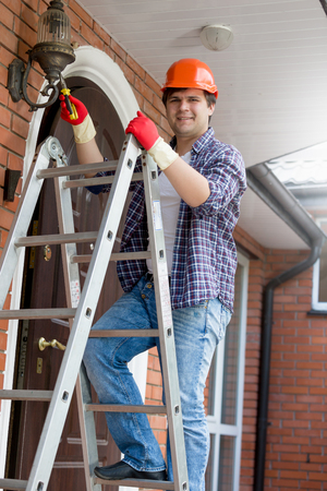 stepladder: Young smiling electrician in hardhat climbing the stepladder