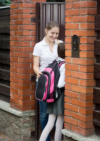niños vistiendose: Retrato de la sonrisa hermosa puerta de apertura madre a su hija va a la escuela Foto de archivo