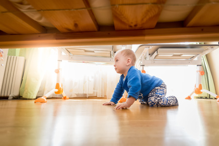 9 months old: Cute 9 months old baby crawling on wooden floor at bedroom Stock Photo