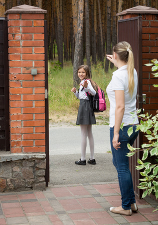 parting off: Young mother waving to her daughter walking at school